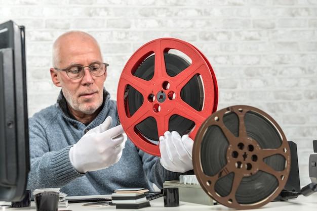 Mężczyzna fotograf patrząc na rolce filmu 16 mm