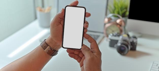 Mężczyzna fotograf pokazuje makiety ekran smartfona siedząc przy biurku z materiałami biurowymi