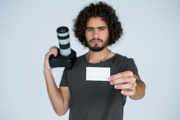Mężczyzna fotograf pokazuje wizytówkę w studio