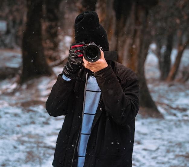 Mężczyzna fotograf przechwytujący zimę w lesie