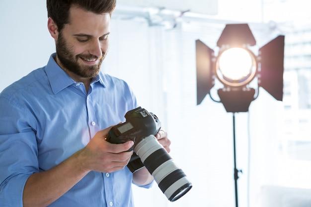 Mężczyzna fotograf przeglądający zdjęcia zrobione jej aparatem cyfrowym