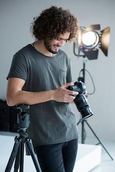 Mężczyzna fotograf przeglądający zrobione zdjęcia aparatem cyfrowym