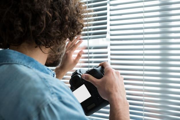 Mężczyzna fotograf z aparatem cyfrowym patrząc przez rolety