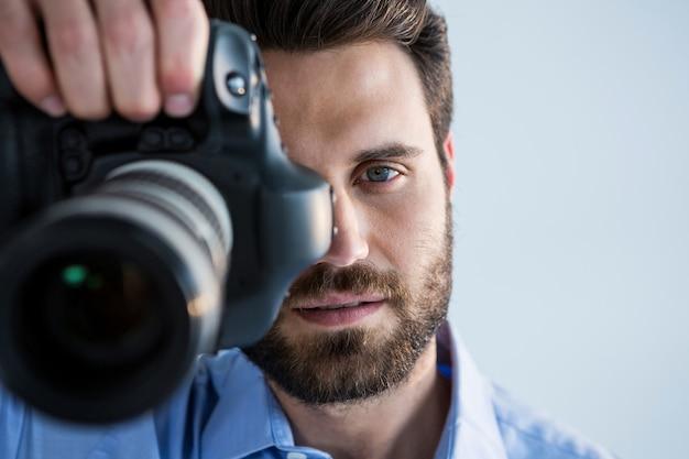 Mężczyzna fotograf z aparatem cyfrowym w studio