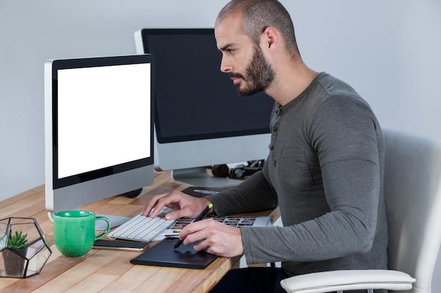 Mężczyzna fotograf za pomocą tabletu graficznego przy biurku
