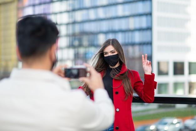 Mężczyzna fotografujący swoją dziewczynę robiącą znak zwycięstwa podczas pandemii krukowicy lub koronawirusa