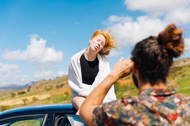 Mężczyzna fotografuje grimacing kobiety obsiadanie na samochodu dachu