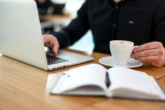 Mężczyzna freelancer pracuje na laptopie w kawiarni. młody człowiek w czarnej koszuli pije kawę, aby się skoncentrować i rozweselić. filiżanka espresso. niewyraźne otwarty pamiętnik na drewnianym stole.