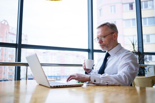 Mężczyzna freelancer pracuje w kawiarni nad nowym projektem biznesowym. siedzi przy dużym oknie przy stole. patrzy na ekran laptopa z filiżanką kawy