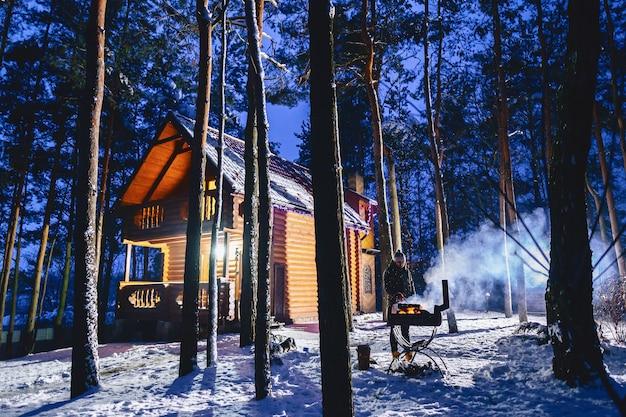 Mężczyzna frytuje mięso z grilla przy chacie wieczorem i w dymie