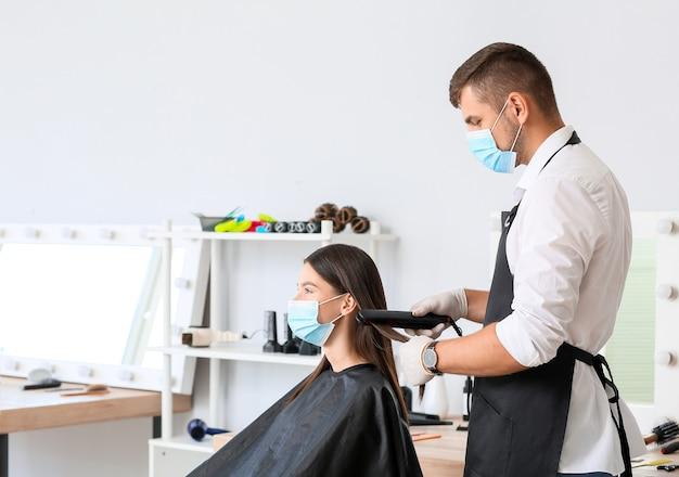 Mężczyzna fryzjer pracuje z klientem w salonie podczas epidemii koronawirusa