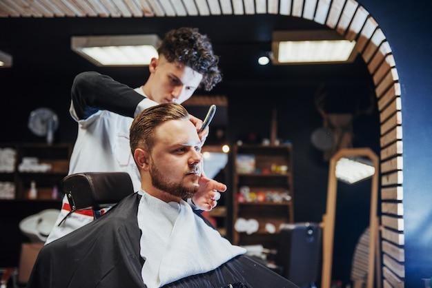 Mężczyzna fryzjer robi strzyżenie brody dorosłych mężczyzn w męskim salonie fryzjerskim