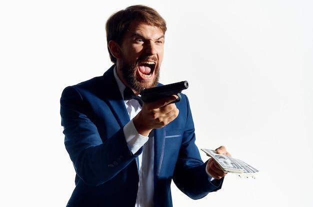 Mężczyzna gangster z plikiem pieniędzy i bronią w dłoni w klasycznym garniturze gangstera.