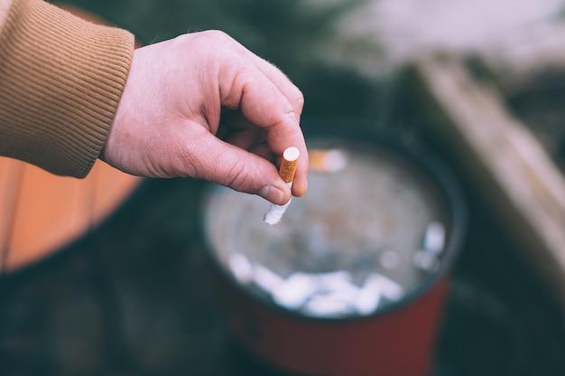 Mężczyzna gasi papierosa do kosza.