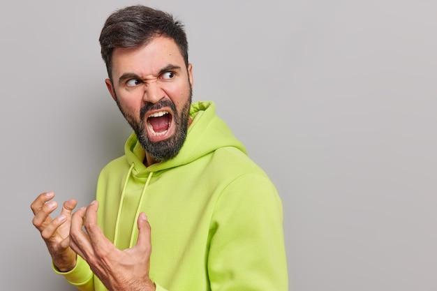 Mężczyzna gestykuluje gniewnie krzyczy głośno wyraża wściekłość nienawidzi coś się odwraca nosi zwykłą bluzę z kapturem pozuje na szaro