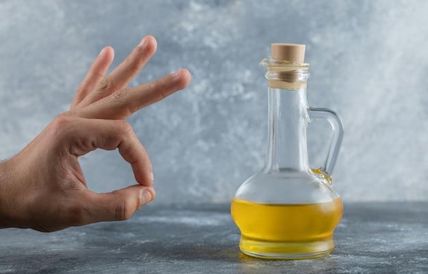 Mężczyzna gestykuluje ok ręką za butelką oleju. wysokiej jakości zdjęcie