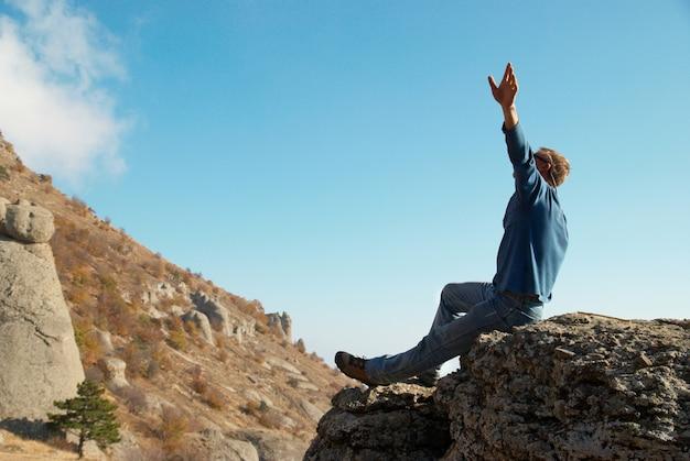 Mężczyzna gestykuluje z uniesionymi rękami na skale w górach