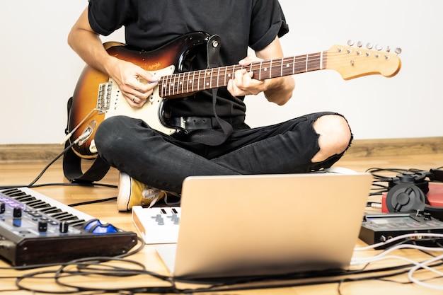 Mężczyzna gitarzysta gra na gitarze elektrycznej w nowoczesnym domowym studiu lub sali prób. młody człowiek produkujący muzykę za pomocą elektronicznych procesorów efektów, syntezatorów i procesorów do laptopów, syntezatora i laptopa