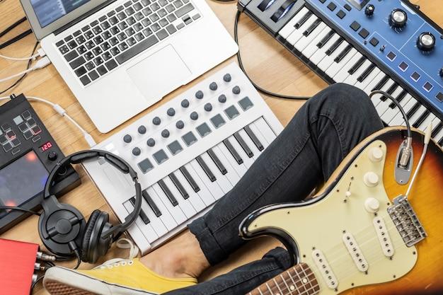 Mężczyzna gitarzysta z gitarą elektryczną w nowoczesnym domowym studiu lub sali prób. młody człowiek produkujący muzykę za pomocą elektronicznych procesorów efektów, syntezatora i laptopa