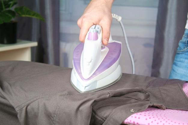Mężczyzna głaszcze bieliznę czarnym żelazkiem elektrycznym na desce do prasowania. gospodarstwo domowe.