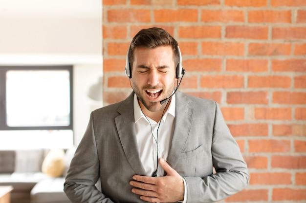 Mężczyzna głośno się śmieje z jakiegoś przezabawnego żartu, czuje się szczęśliwy i wesoły, dobrze się bawi