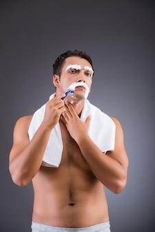 Mężczyzna golenia na ciemnym tle
