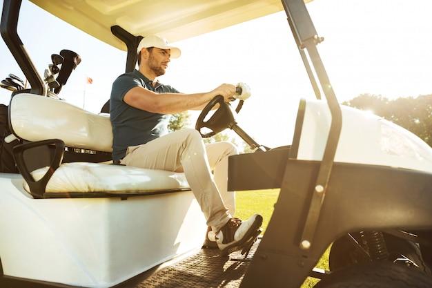 Mężczyzna golfista jazdy wózkiem z kijami golfowymi