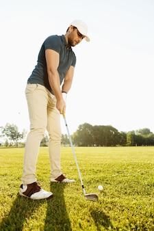 Mężczyzna golfista o tee off piłeczki golfowej