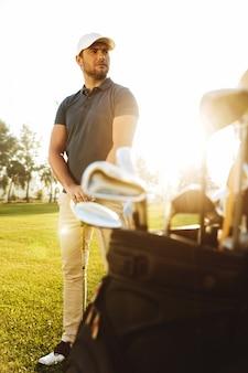 Mężczyzna golfowy gracz przy zielonym polem z klubowym workiem