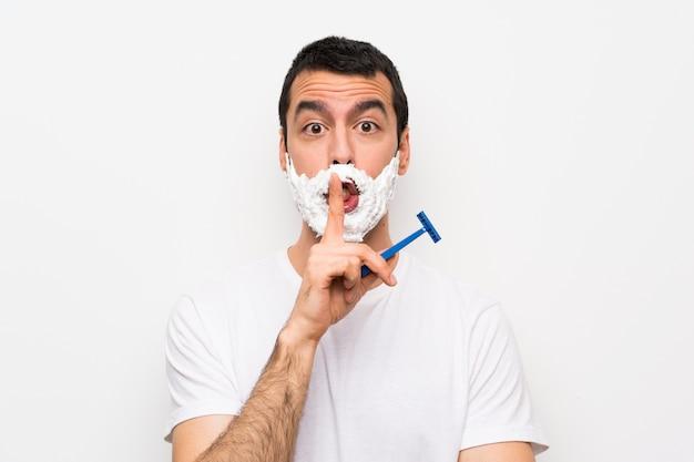 Mężczyzna goli brodę nad odosobnioną biel ścianą pokazuje znak cisza gesta kładzenia palec w usta