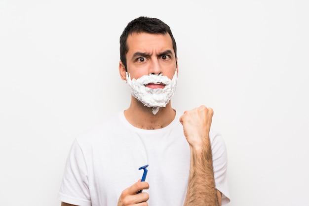 Mężczyzna goli brodę nad odosobnioną biel ścianą z gniewnym gestem