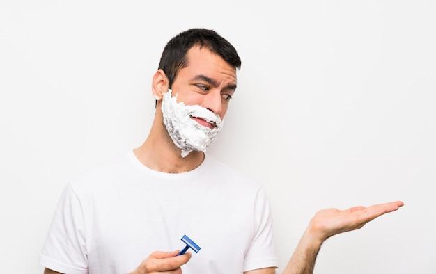 Mężczyzna goli brodę nad odosobnionym biel ściany mienia copyspace z wątpliwościami