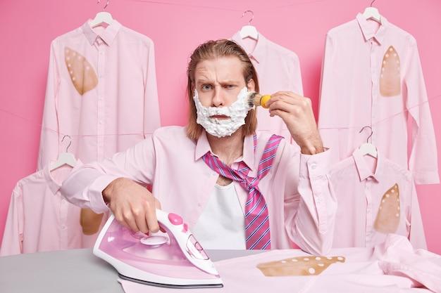 Mężczyzna goli brodę wygląda z niezadowolonym wyrazem twarzy nosi koszulę i krawat na szyi używa parowego żelazka elektrycznego do głaskania stojaki na ubrania w pobliżu deski do prasowania