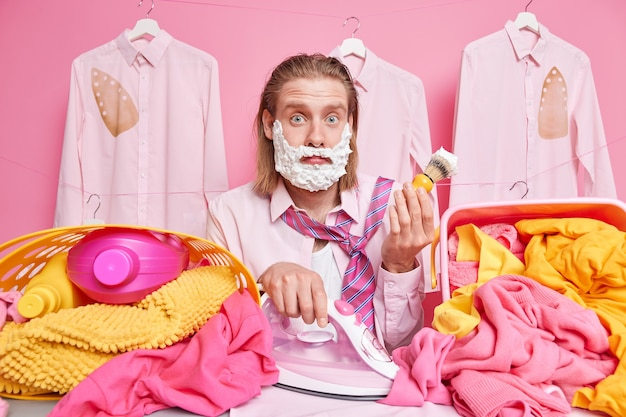 Mężczyzna goli się robi pranie i prasowanie jednocześnie zajęty pracami domowymi ma niezrozumiałe, zdezorientowane wyrazy twarzy na wyprasowanych spalonych koszulach wiszących na sznurku