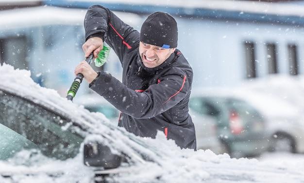 Mężczyzna gorączkowo zeskrobuje lód z zamarzniętych szyb swojego samochodu zaparkowanego na zewnątrz.