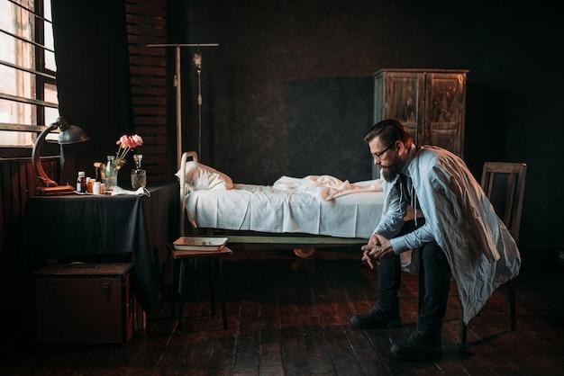 Mężczyzna gość przed pustym łóżkiem szpitalnym