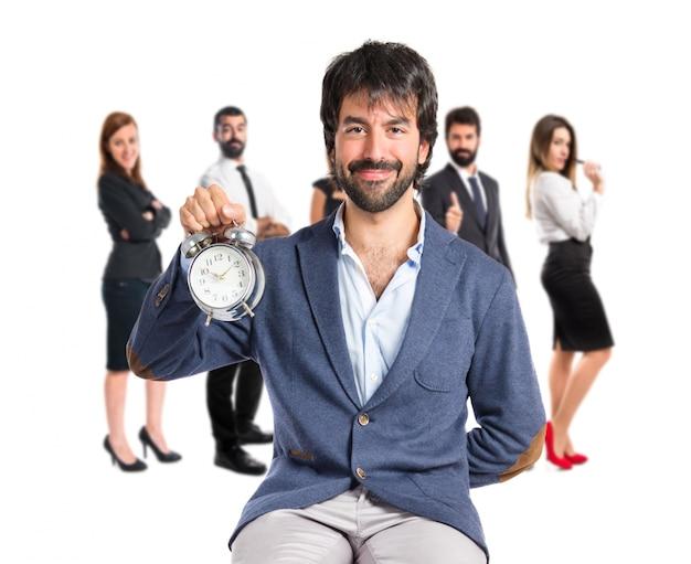 Mężczyzna gospodarstwa zegara na białym tle