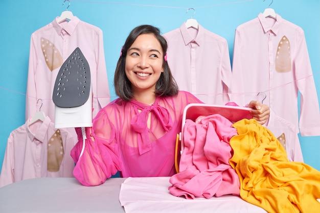 Mężczyzna gospodyni trzyma żelazko elektryczne pozuje przy desce do prasowania ze stosem pogniecionego wypranego prania uśmiecha się szeroko zadowolona z efektów swojej pracy głaszcze rodzinne ubranie