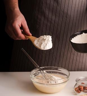 Mężczyzna gotować, dodając mąkę do mieszanki
