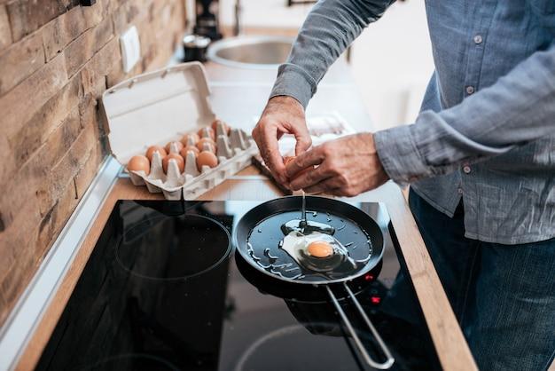 Mężczyzna gotowania jajek na śniadanie, stojąc w kuchni w domu.