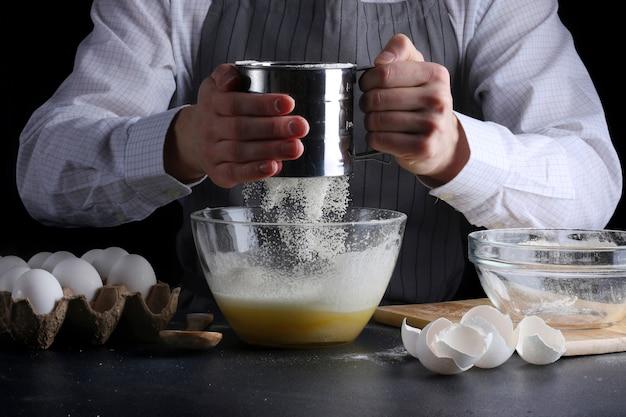 Mężczyzna gotuje ciasto i przesiewanie mąki w misce