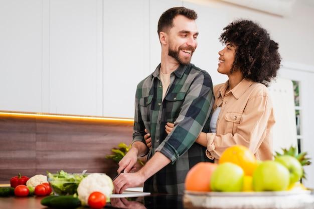 Mężczyzna gotuje i patrzeje jego dziewczyny