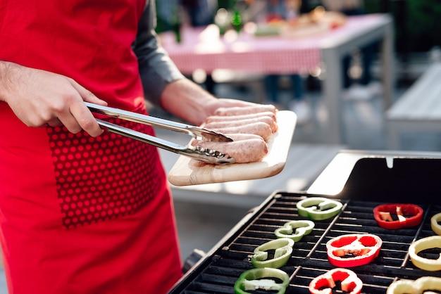 Mężczyzna gotuje kiełbaski na grillu na imprezie przyjaciół.