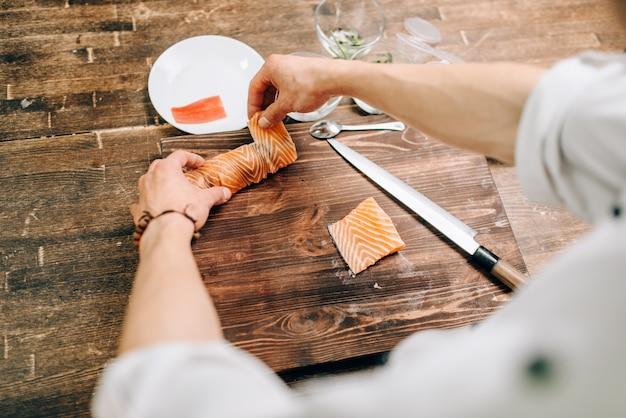 Mężczyzna gotuje owoce morza na drewnianym stole, proces przygotowania kuchni japońskiej. tradycyjna kuchnia azjatycka, robienie sushi