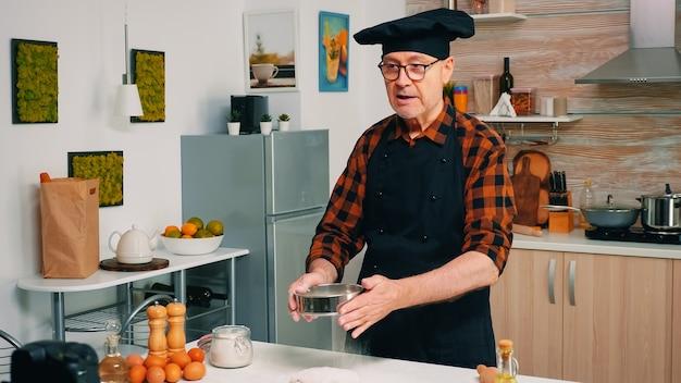 Mężczyzna gotuje przed profesjonalnym cyfrowym aparatem bezlusterkowym z blogiem wideo nagrywania mikrofonu. emerytowany szef kuchni wykorzystujący komunikację internetową, kręcenie blogów w mediach społecznościowych