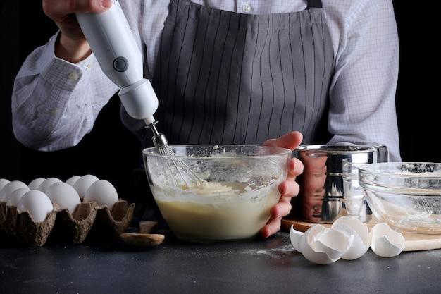 Mężczyzna gotuje przesiewanie mąki w dziobie