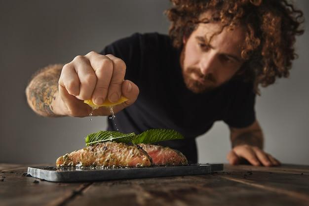 Mężczyzna gotuje zdrowy posiłek, wyciska limon na dwóch surowych kawałkach łososia udekorowanych listkiem mięty w białej sosie winnej z przyprawami i ziołami na marmurowym tarasie przygotowanym do grillowania