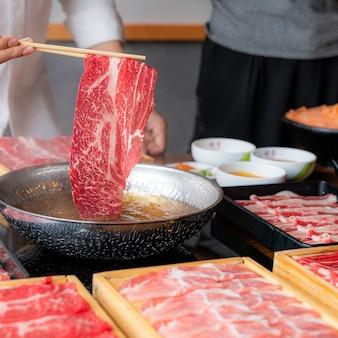 Mężczyzna gotuje zestaw sukiyaki z japońskiej wołowiny wagyu