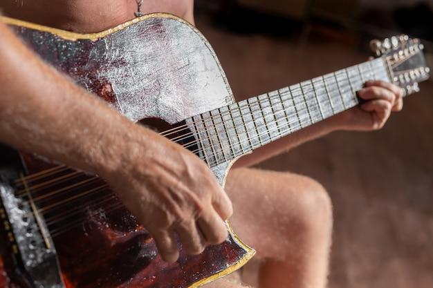 Mężczyzna gra na dwunastostrunowej gitarze akustycznej hobby i rozrywka