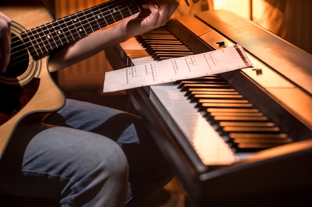 Mężczyzna gra na gitarze akustycznej i fortepianie z bliska
